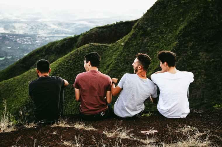four men sitting on ground